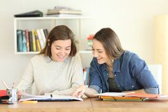 Two students studying together helping each other. Front view portrait of two happy students studying together helping each other reading notes in a notebook on Stock Photo