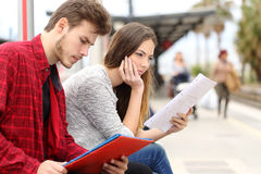 Two students studying waiting transport in a train station Stock Photos