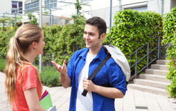 Two students talking on campus. With university building in the background Royalty Free Stock Photography