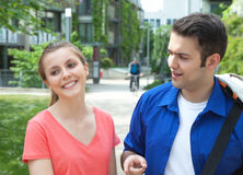 Two students talking about education. Outside in a park on the campus with meadow and trees in the background Royalty Free Stock Photos