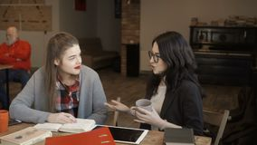 Young girl talks with friend sitting at the table. Two students are talking sitting at the table. Pretty girls have a break during preparation to the exams at stock video