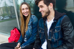 Two students talking in the street after class. Stock Images
