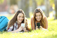 Two students texting in their smart phones in a park. Front view of two students texting in their smart phones lying on the grass in a park stock photo