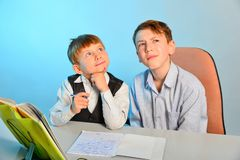 Two students think about the eternal, two students do their homework and look up.  royalty free stock photo