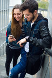 Two students using mobile phone in the street. Stock Images