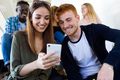 Two students using they mobile phone in a university. Stock Image