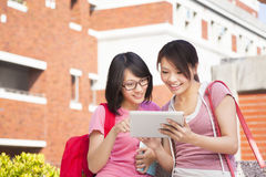 Two students using a tablet to discuss homework. At campus Royalty Free Stock Images