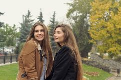 Two students walk in the autumn park and have fun. They have long brown hair and look fashionable and modern Stock Photo