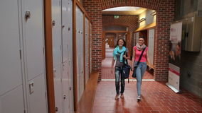 Two students walking down hallway to locker. In college stock video