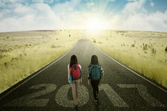 Two students walking with sunrise on the road Royalty Free Stock Photos