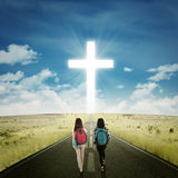 Two students walking toward a cross Royalty Free Stock Images