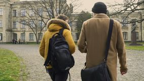 Two students walks near university. Two students walks in park near the university. Friends are discussing some educational material. Young people talks with stock video footage