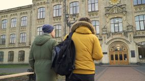 Two students walks to the university. Friends are discussing some educational material. Young people talks with each other about exams at university. Guys have stock video footage