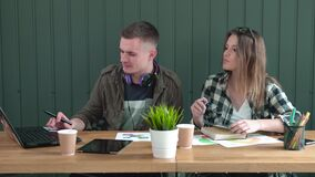 Students Work in Office. Two students working in modern green office, long-haired woman taking notes, fair-haired boy searching information on the internet stock footage
