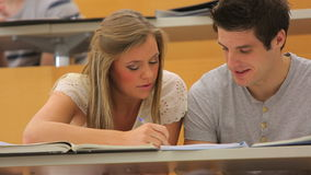 Two students working in team. Students working in team with books in the lecture hall stock footage