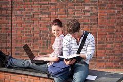 Two students working together with book and laptop Royalty Free Stock Photo