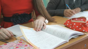 Two students write in exercise book with ball pen. Two students sit at school desk and write in exercise book with a ball pen stock video footage