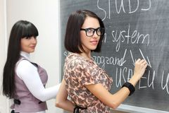 Two students writing on the blackboard Stock Photography