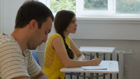Two students writing notes in the classroom. stock footage