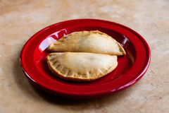Two stuffed pie tarts on a red plate. selective focus, shallow depth of field Stock Photography