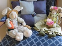 Two stuffed toy rabbits dressed up and waiting for Easter. These stuffed rabbits are dressed in their finest Easter outfits.They are relaxing in a chair, with a Stock Image