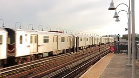 Two stunning modern urban downtown steel subway metro trains meet arriving at railway neighborhood station on cloudy day. Two amazing modern urban downtown steel stock footage