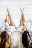 Two stunning women talking on phones with their hair falling off Royalty Free Stock Photo