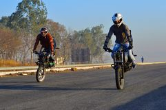 Two stunt motorcycle riders making stoppie near Pune royalty free stock photos