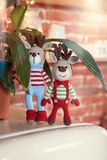 Two stylish amigurumi deers in striped sweaters, scarf and butterfly tie standing near flowerpot. Children toys. Two stylish amigurumi deers in striped sweaters stock image