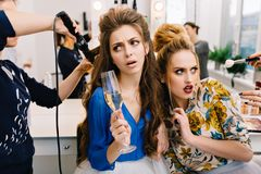Two stylish astonished models in beauty salon during preparation to party. Fashionable coiffure, hairdresser service stock photos