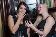 Two stylish beautiful women looking at a mobile Stock Photography