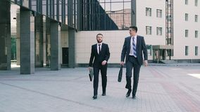 Two stylish business men wearing smart suits walking to the office talking about coming meeting. They are confident and looking forward to the meeting. Slow stock video