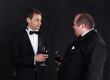 Two stylish businessman in tuxedos with glasses of red wine Stock Photos