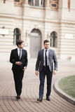 Two stylish businessmen speaking and smiling outdoors Stock Images