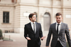 Two stylish businessmen speaking and smiling outdoors Stock Photo
