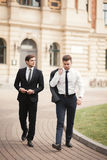 Two stylish businessmen speaking and smiling outdoors Royalty Free Stock Photos