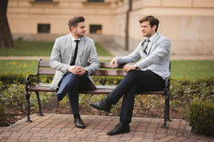 Two stylish businessmen speaking and smiling outdoors Stock Photos