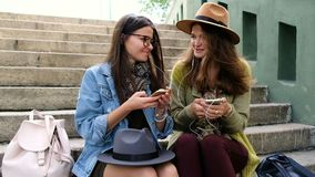 Two female friends sharing smartphone to listen music and dancing. Two stylish female friends sharing smartphone to listen music in the park stock footage