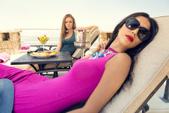 Two stylish girls sitting in beach chairs enjoying the tropical weather Royalty Free Stock Photo