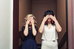 Two stylish girls stand with eyes closed with hands. Two stylish girls stand with eyes closed with hands stock photos