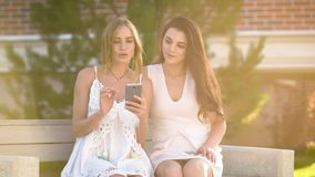 Two stylish girls in white dresses sitting on bench and sharing smartphone in sunlight of summer. stock video
