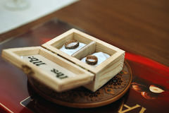 Two stylish golden engraved rings in wooden box Stock Photos