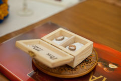 Two stylish golden engraved rings in wooden box Royalty Free Stock Photos