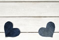 Two stylish hearts are cut from blue denim fabric lying on a wh Royalty Free Stock Image