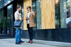 Two Stylish Men Chatting Outdoors. Full length portrait of two elegant young businessmen wearing autumn coats chatting outdoors in city streets, copy space stock photo