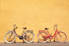 Two stylish new bicycles near color. Wall outdoors Stock Images