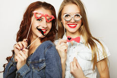 Two stylish sexy hipster girls best friends ready for party. Over gray background Stock Image