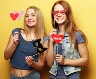 Two stylish sexy hipster girls best friends ready for party. Over yellow  background Stock Photos