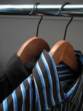 Two stylish shirts on wooden hangers Royalty Free Stock Image