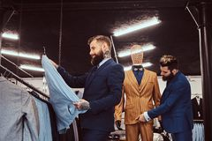 Two stylish shop assistants elegantly dressed working in a menswear store. Two stylish shop assistants elegantly dressed working in menswear store stock photography